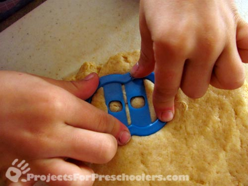 use alphabet cookie cutters to cut out doughnut shapes